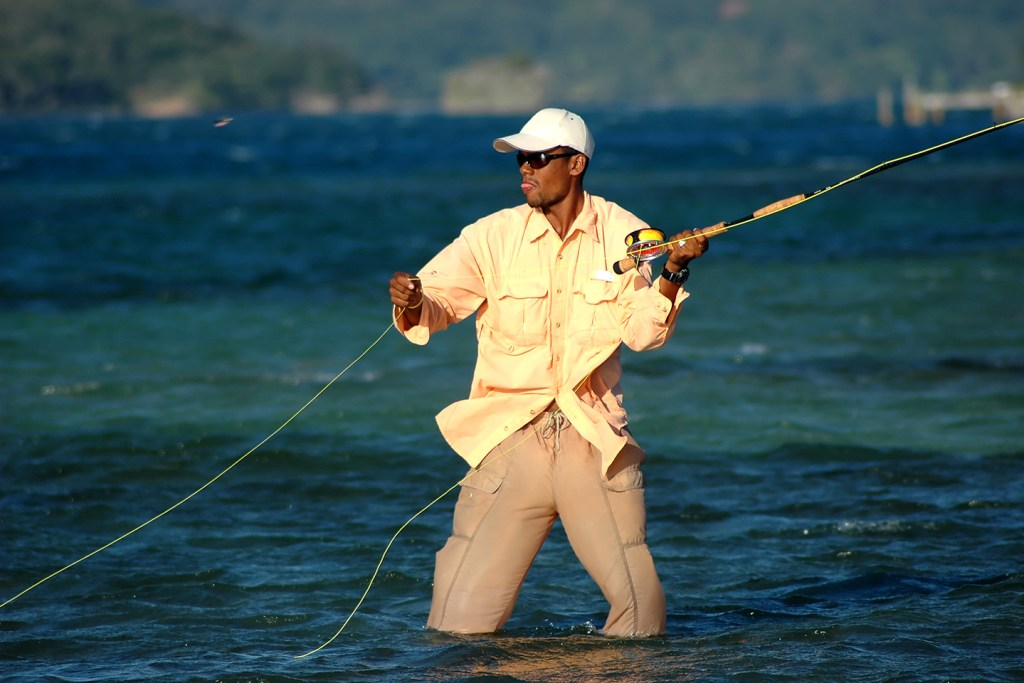 A fly fisherman wading in shallow water while fishing in the Bahamas