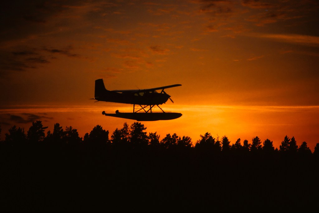 A float plane flying over a forest at sunset