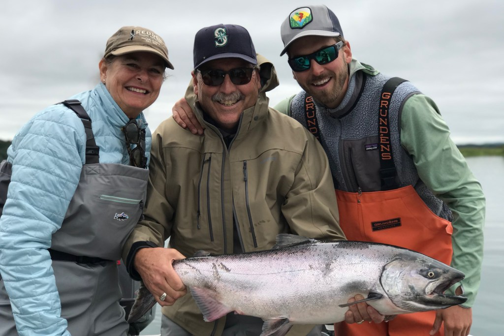 Three anglers holding a large King Salmon