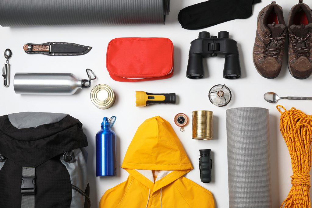 An assortment of objects needed for a trip to a fly-in fishing outpost: raincoat, camping gear, hiking shoes, a backpack, and more