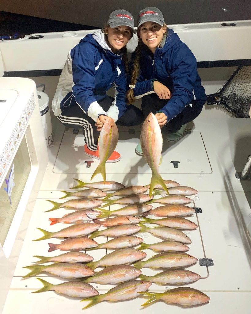 Emily and Amanda Gale on a boat with a large number of Yellowtail Snapper