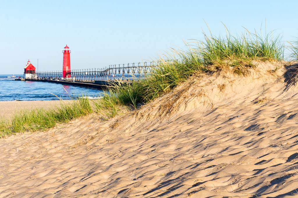 A yellow sandy beach in Grand Haven, Michigan, with a red lighthouse next to the water in the distance