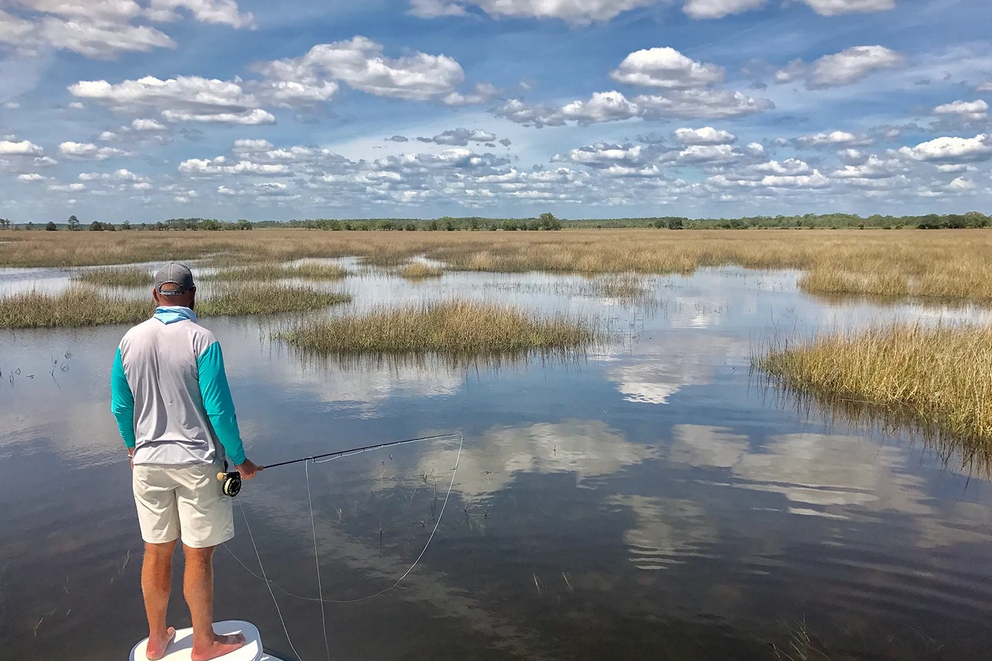 A fly fisherman standing at the front of a boat with shallow flats and sea grasses extending into the distance