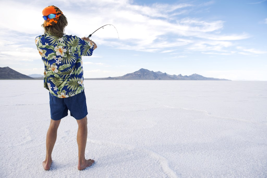 A man in shorts and a Hawaiian holding a rod on a sheet of ice, showing the classic setup for many funny fishing jokes.