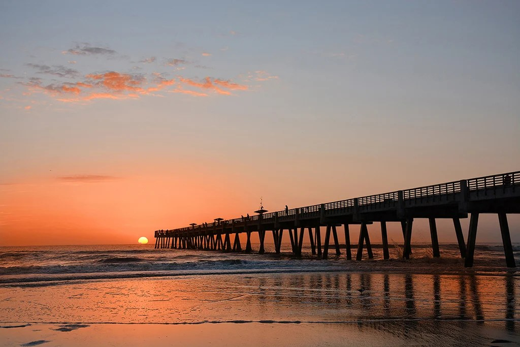 A long, wooden fishing pier at sunset