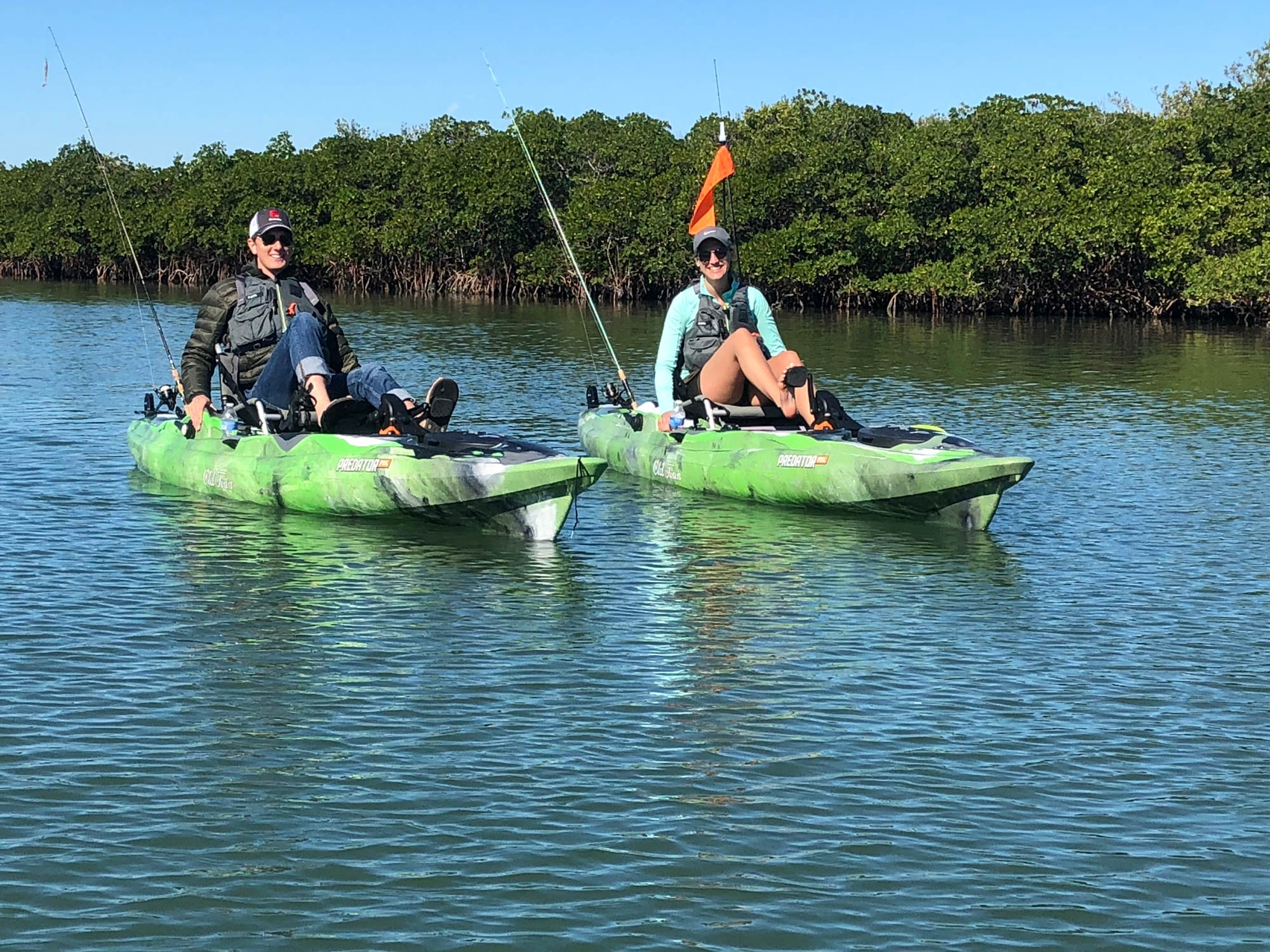 Two anglers on kayaks paddling side by side