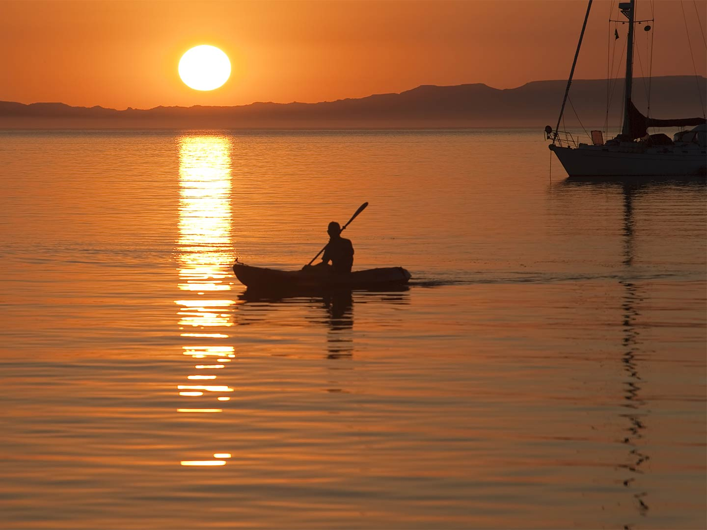 A kayaker paddles along the calm inshore waters out of La Paz as the sun sets
