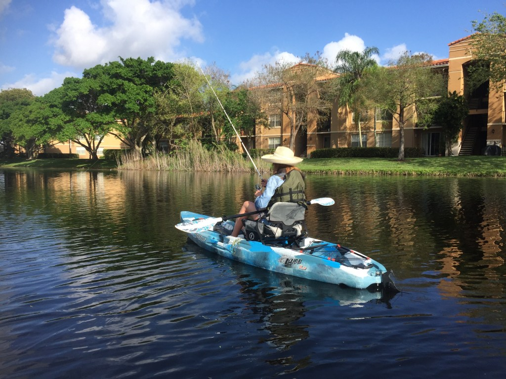 An angler fishing on a kayak in a canal