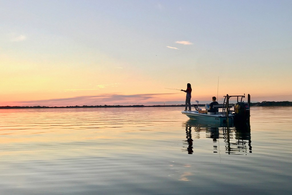 A boat on the calm waters of Lake Butler, Florida at sunset. An angler is casting his rod off the front of the boat and another man is sitting in the boat watching the sunset.