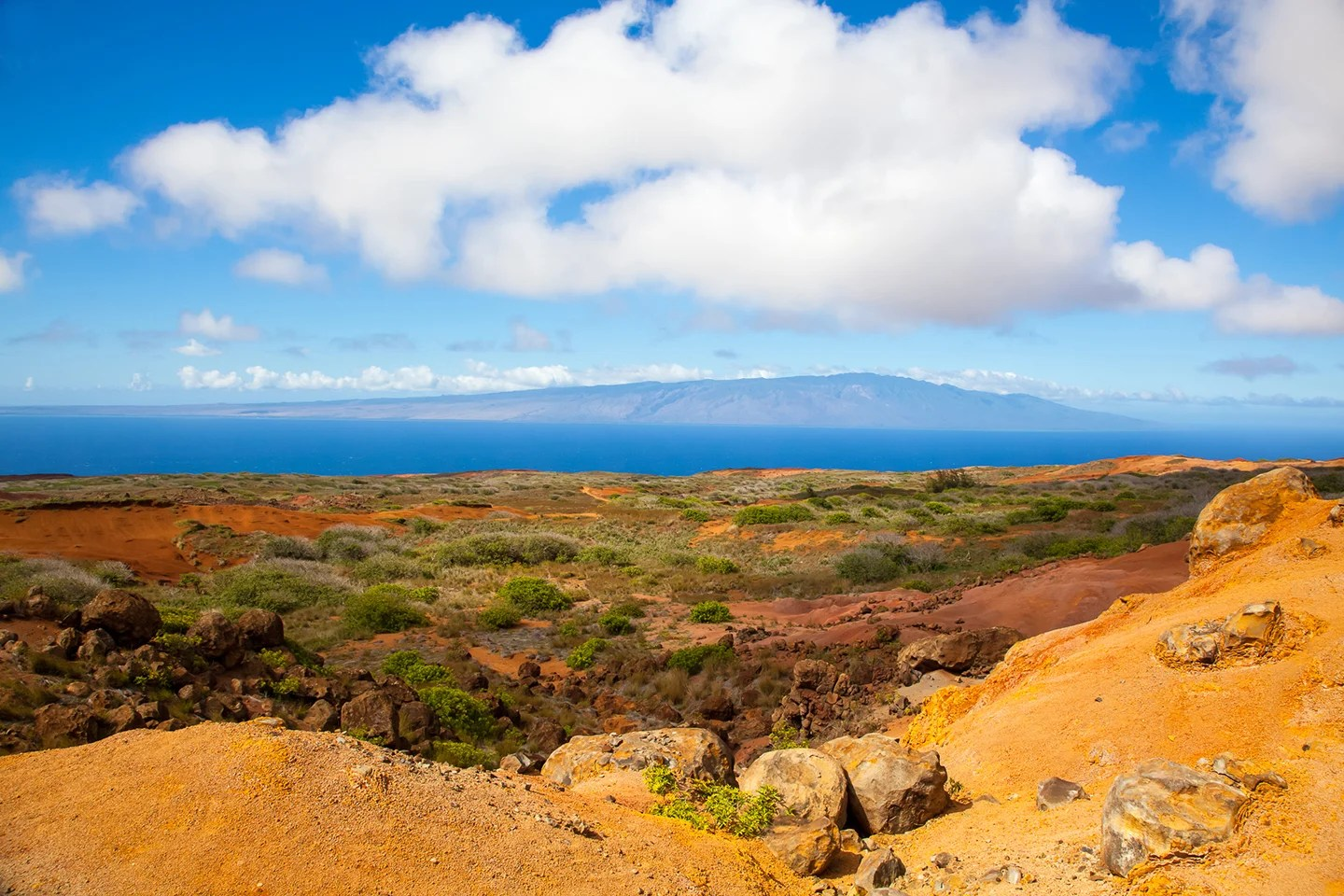 A view across dry land towards the sea on the island of Lanai, Hawaii, with the island of Maui in the distance.