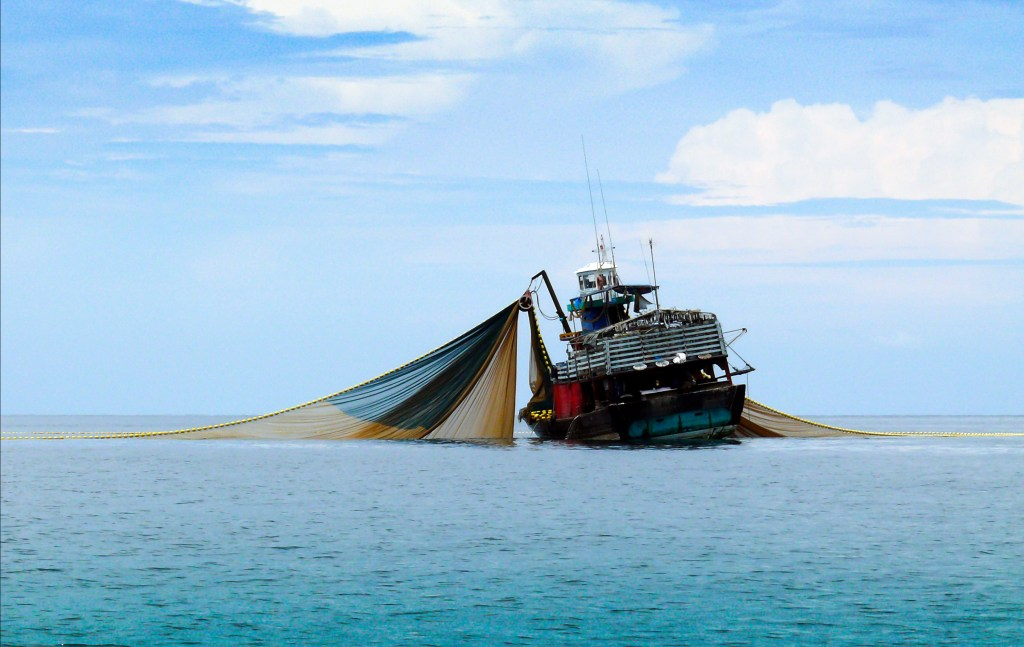 a large trawling boat with its nets in the water