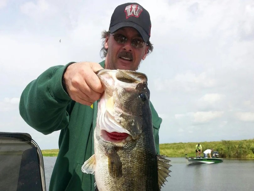 A man displays a Largemouth Bass he has hooked on the river