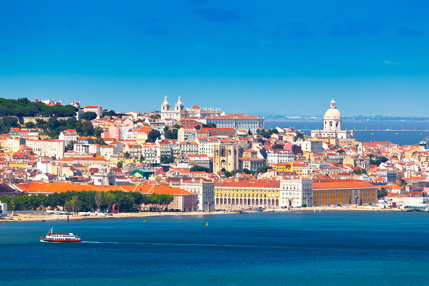 Old buildings in Lisbon, Portugal, taken from the sea with a boat in the bottom left of the photo.