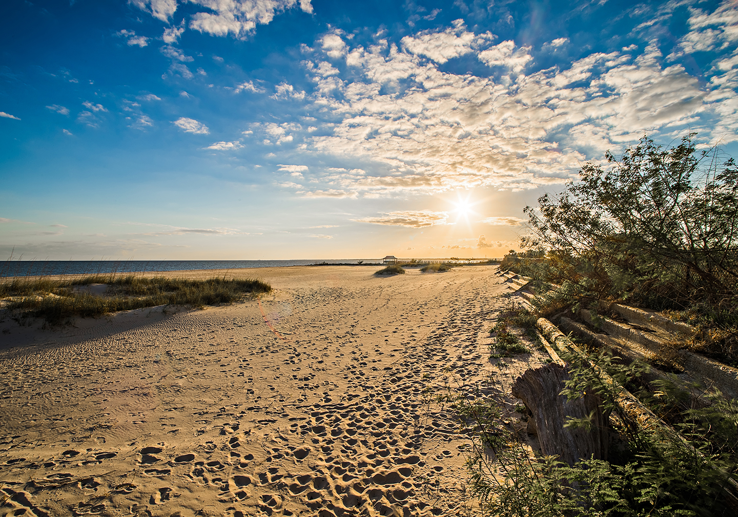 A yellow sandy beach in Long Beach, MS with blue sky and a setting sun in the distance.