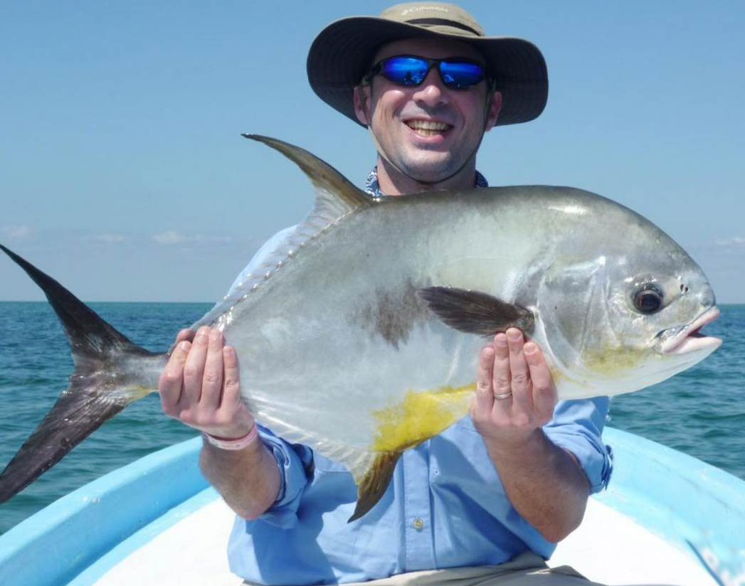 A man holds a big Permit on a flats boat and smiles, with the bay behind him