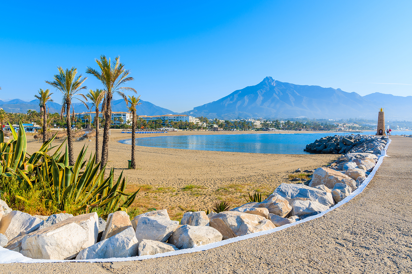 A beach in Marbella, Spain, with palm trees on the left, a walkway on the right, and a mountain in the distance.