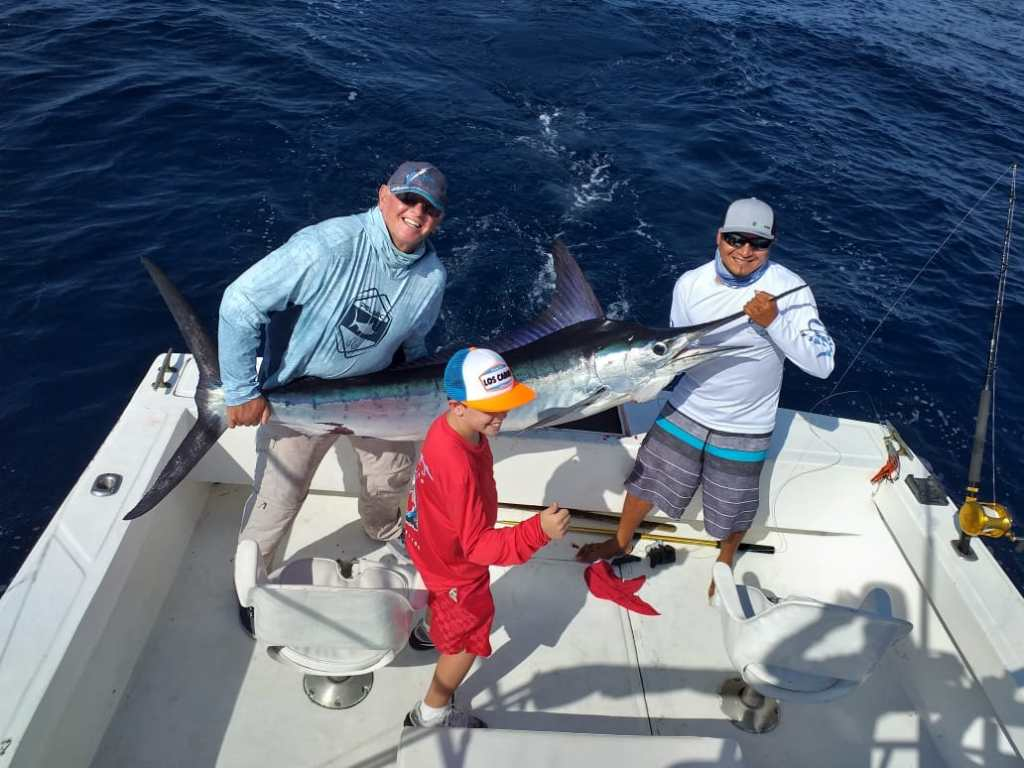 Father and a Cabo fishing guide holding a Marlin, with the son smiling next to them