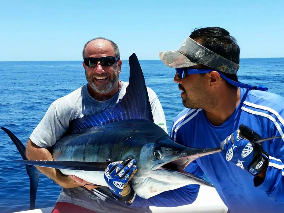 Two anglers hold a Marlin caught fishing the Sea of Cortez
