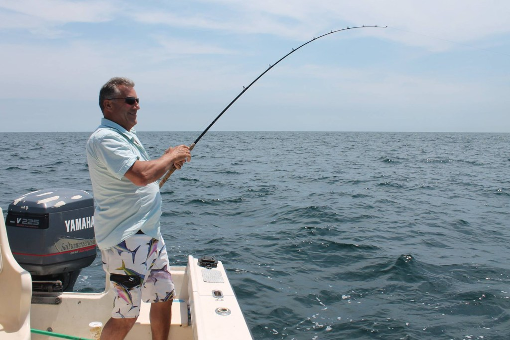 An angler in shorts and a shirt fishing over the side of a boat in the sea