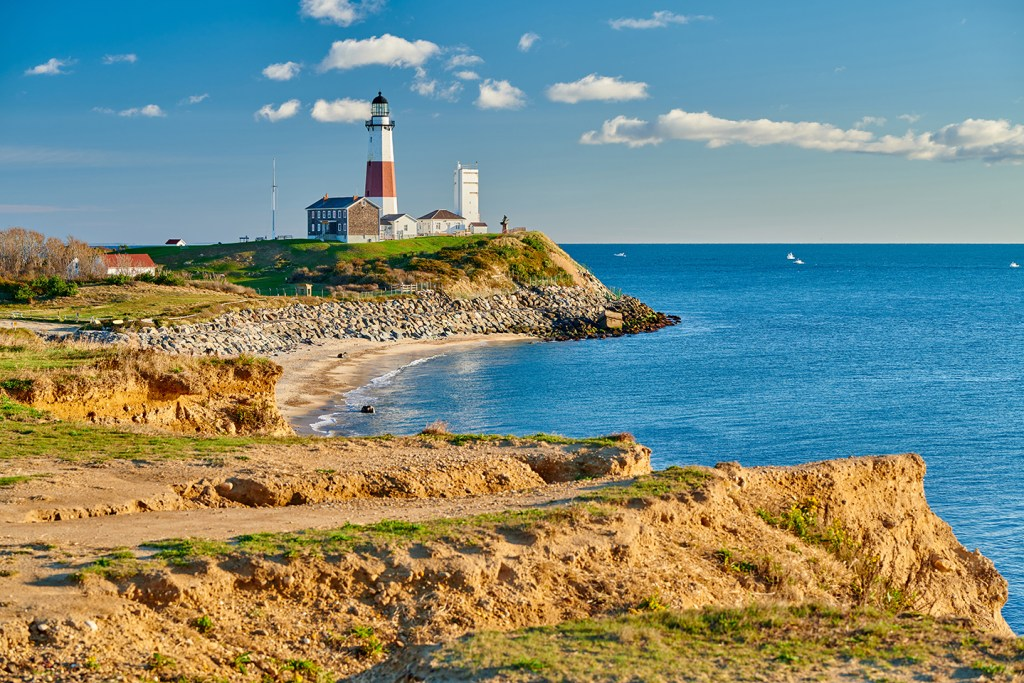 Cliffs by the sea in Montauk, NY, with a lighthouse in the center and sailboats in the distance
