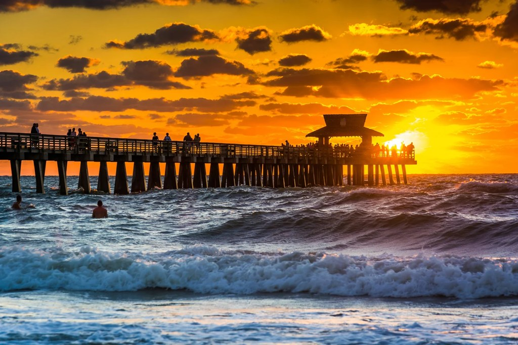 A fishing pier at sunset, with waves crashing on the beach in the foreground and the sun setting into the sea in the distance