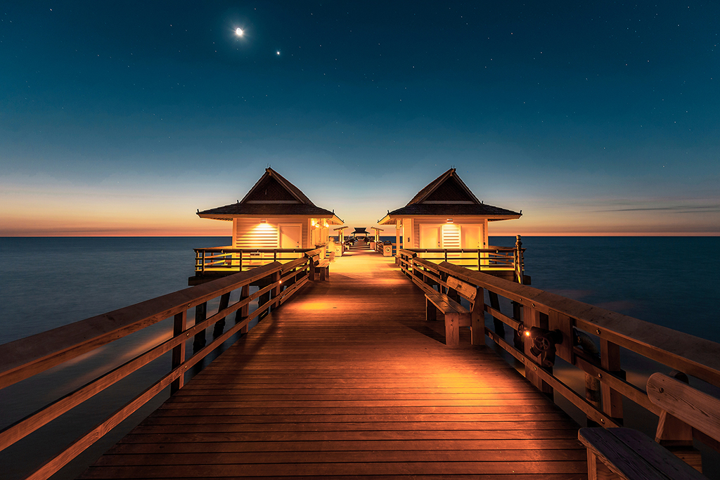 A warmly-lit fishing pier at dusk, with the last light of day on the horizon and stars in the sky above