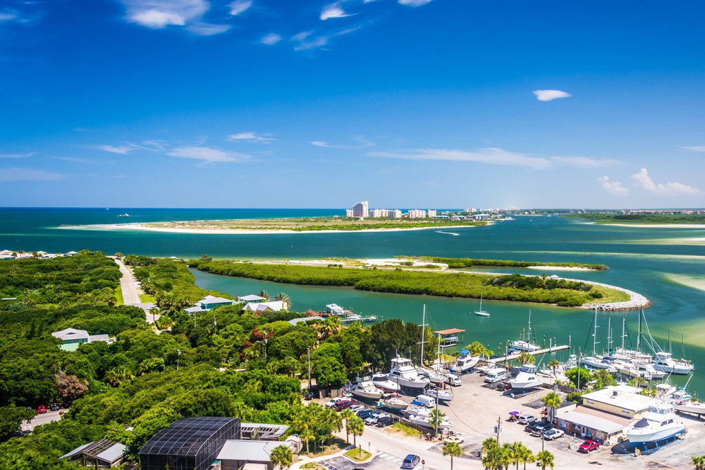 A charter fishing marina in New Smyrna Beach, FL, with boats out of the water in the bottom right, dense green trees on the left, and several green islands in the shallow sea in the center. Buildings are visible in the distance