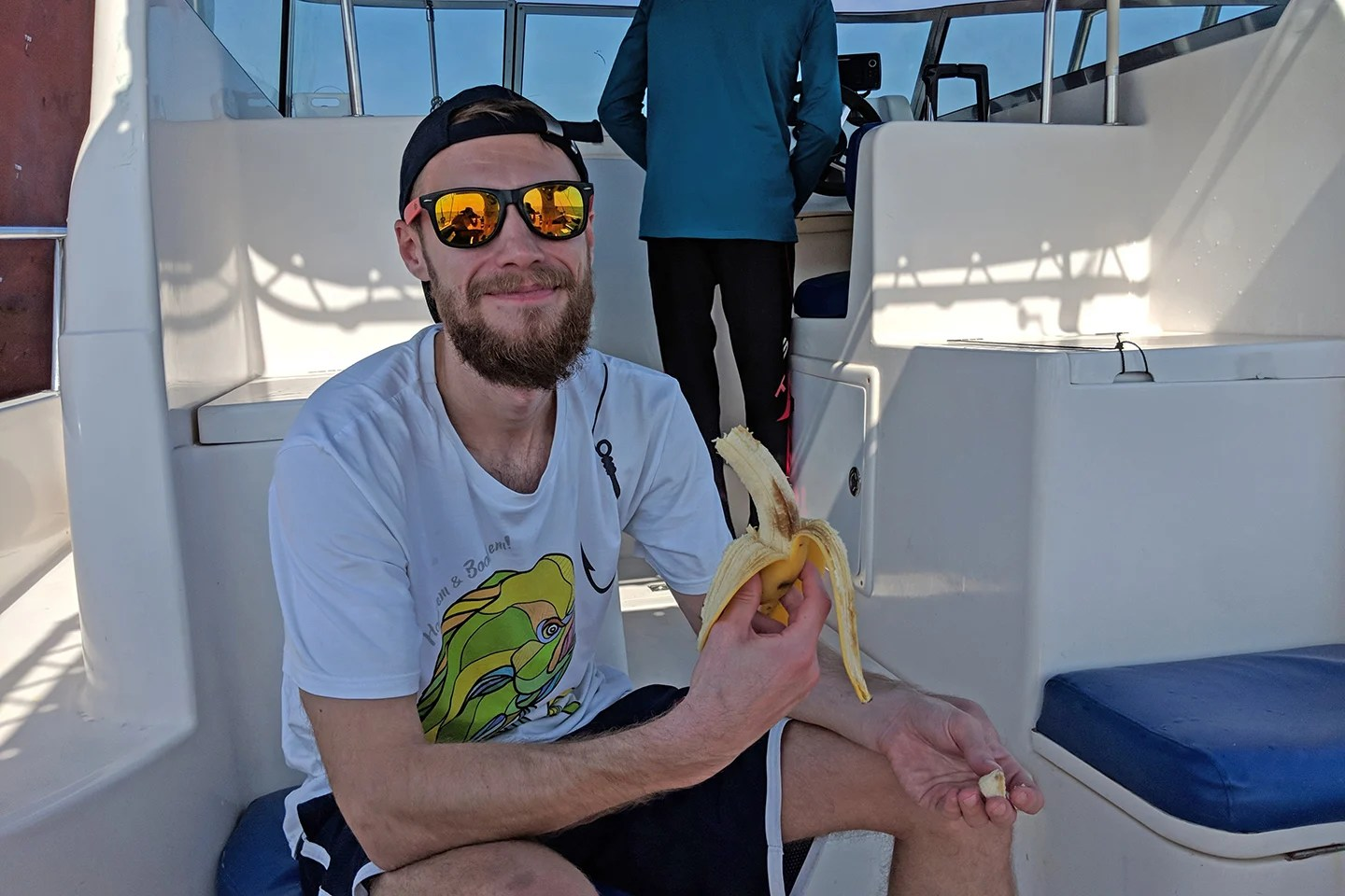 A male angler in a cap and sunglasses eating a banana on a charter fishing boat