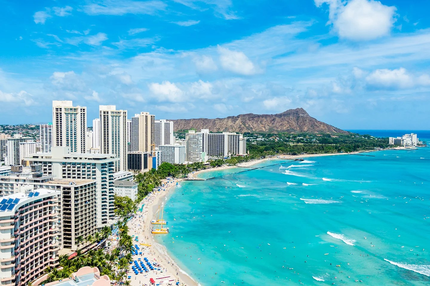 An aerial view of Waikiki Beach in Honolulu, Hawaii, with white tower blocks on the left, bright blue sea on the right, and Diamond Crater mountain in the distance.