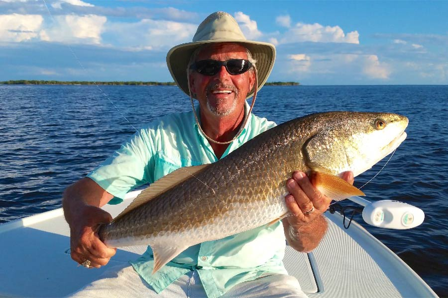 A man holds a Redfish caught in the inshore waters out of Panama City Beach