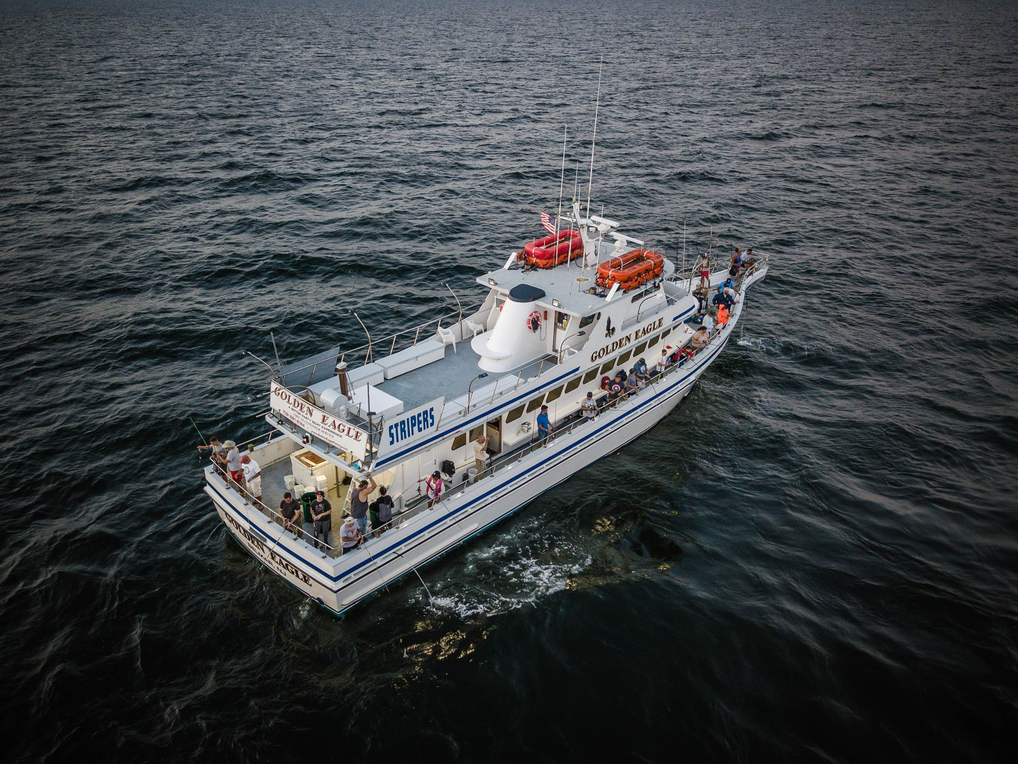 Aerial photo of a party boat taking a large group of anglers out to the fishing grounds