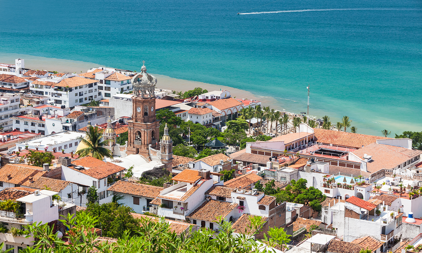 A view over the old town in Puerto Vallarta, Mexico looking toward the sea with a boat in the distance.