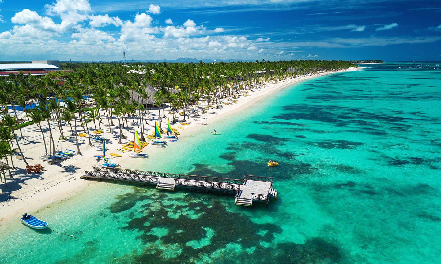 A view from above of the beach at Punta Cana, Dominican Republic, with palm trees and a small pier going into the water.