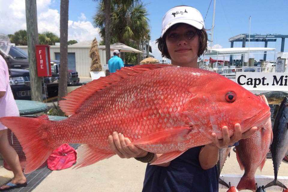 A young woman holds a Red Snapper in Lighthouse Marina