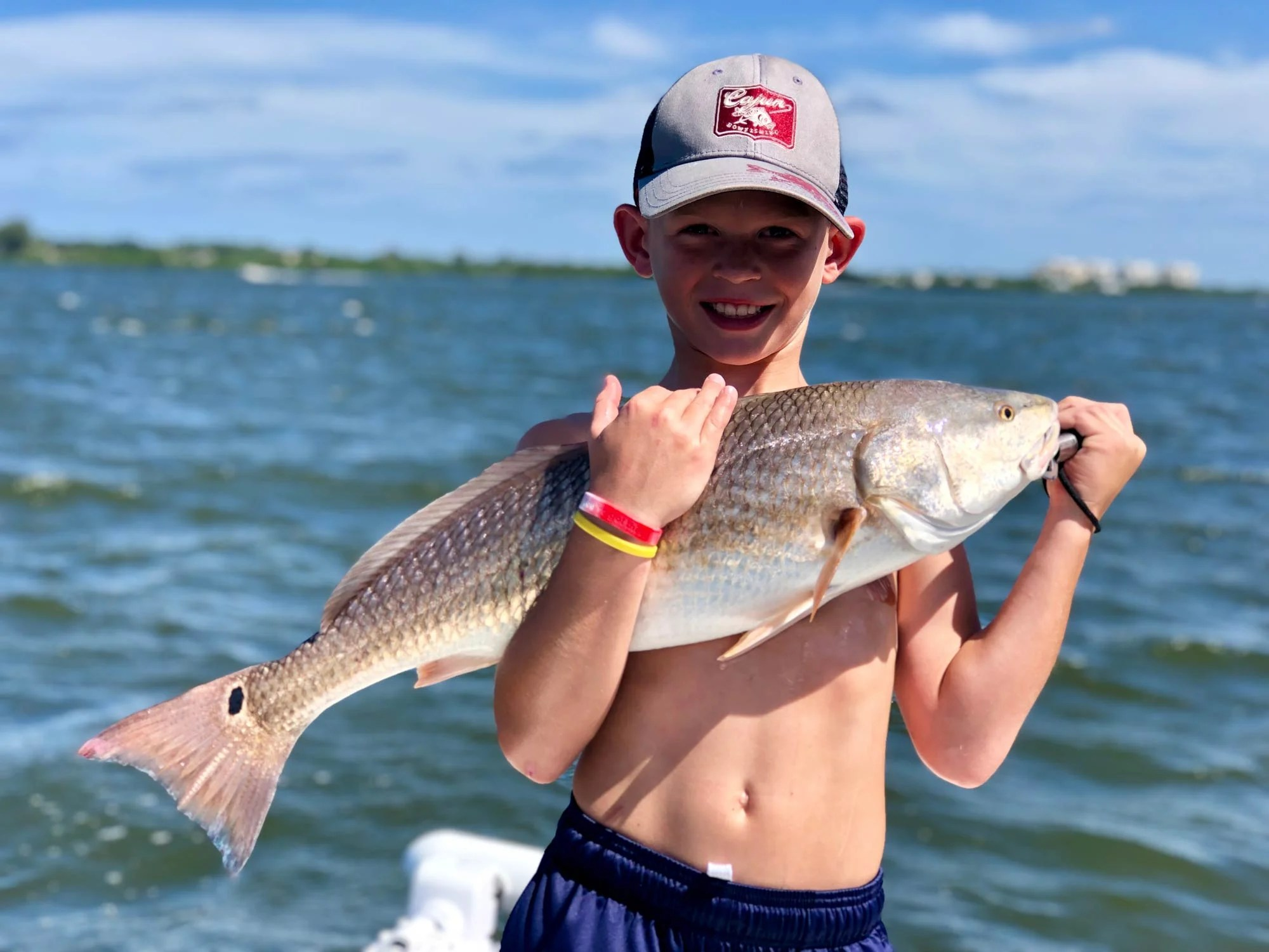 A smiling young angler holding a Redfish on a boat