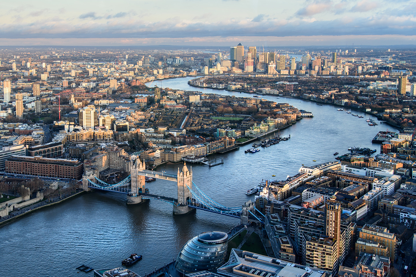An aerial view of the River Thames in London, with Tower Bridge in the foreground and Canary Wharf in the distance
