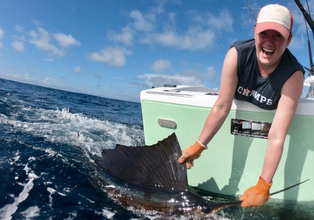 An angler leaning over the side of a boat to pose with a Sailfish, one of the Florida state fish
