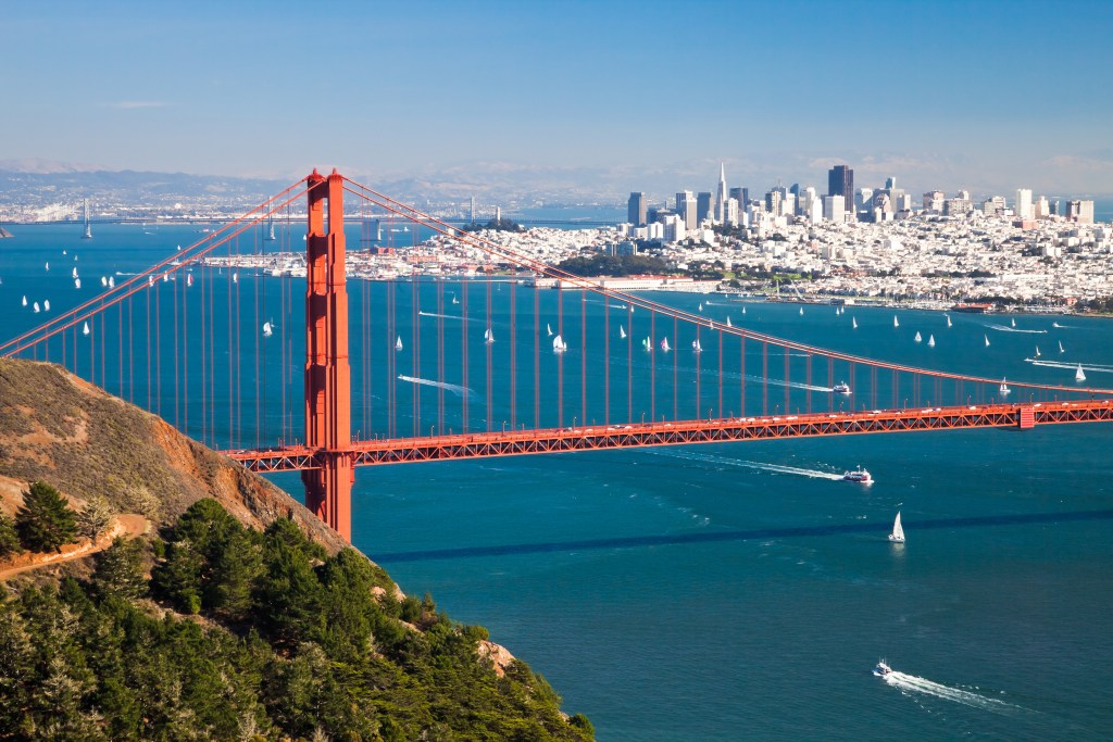 An aerial view of the Golden Gate Bridge, with boats in the bay and San Francisco in the distance