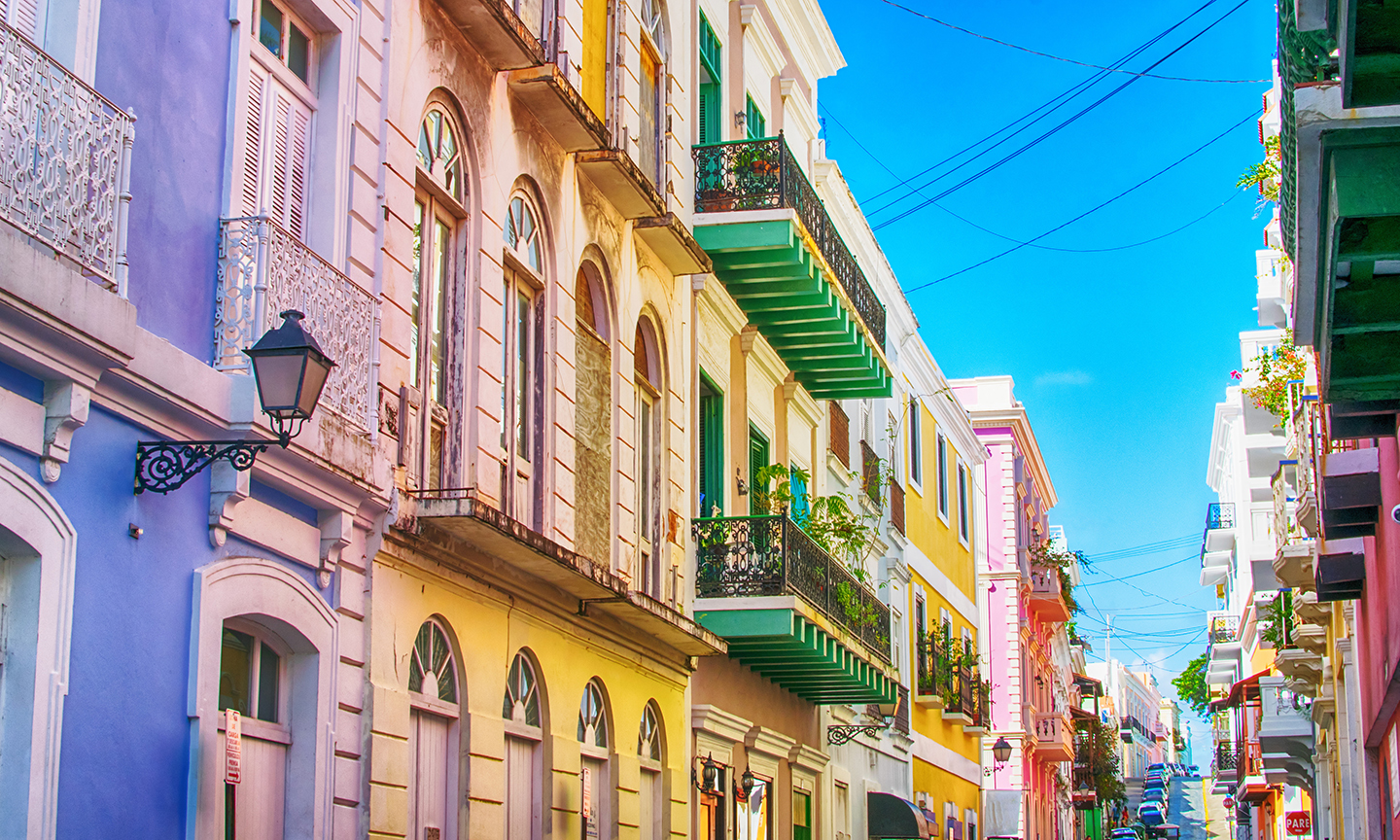 A typical street in Old San Juan, Puerto Rico, with colorful buildings and blue sky.