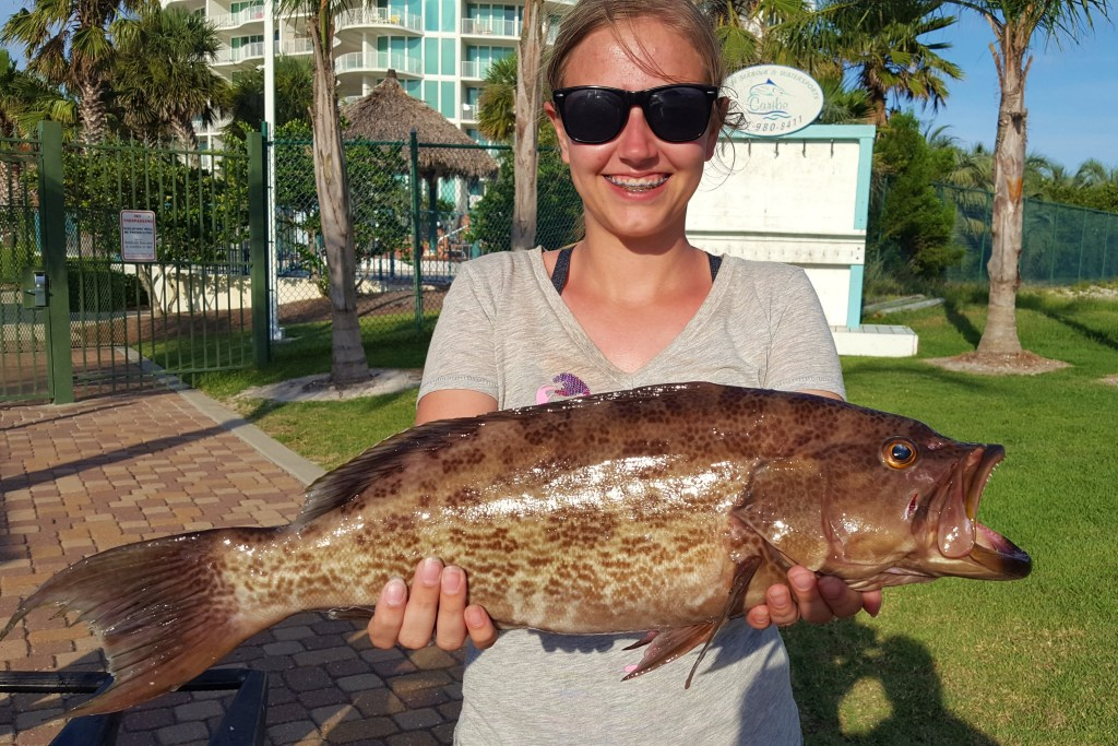 A lady angler holding a Scamp Grouper