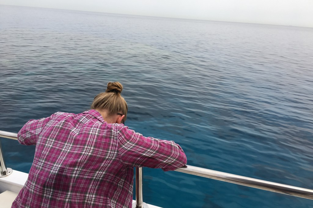A seasick woman leaning over the rail of a boat