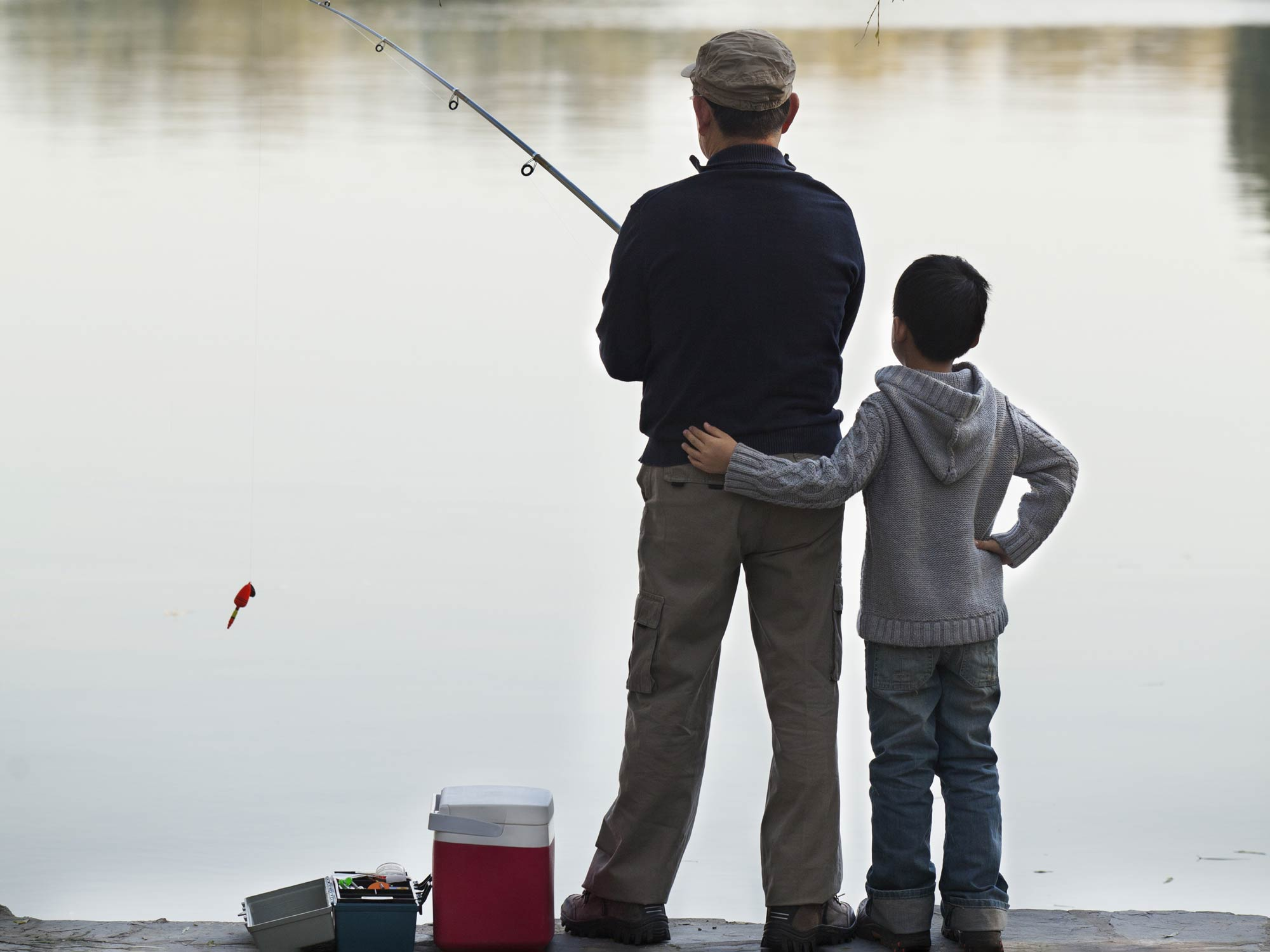 Man and a boy fishing from the shore together