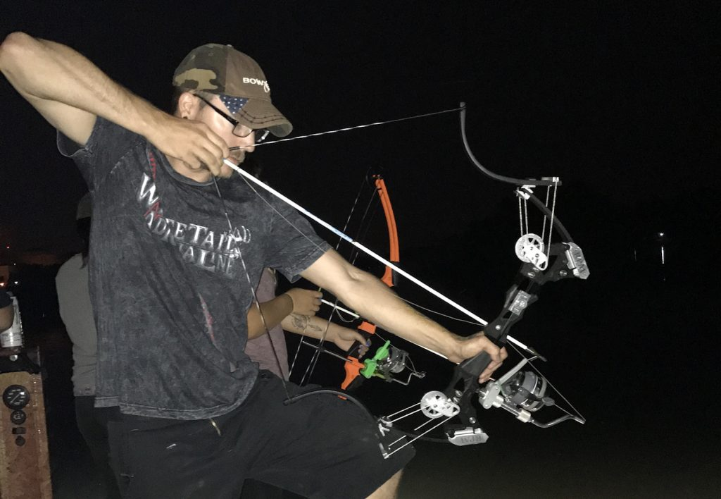 a bowfisher aiming down at the water