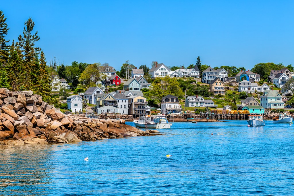 The traditional lobster fishing village of Stonington, Maine, with blue water in the foreground and rocky shore and trees on the left