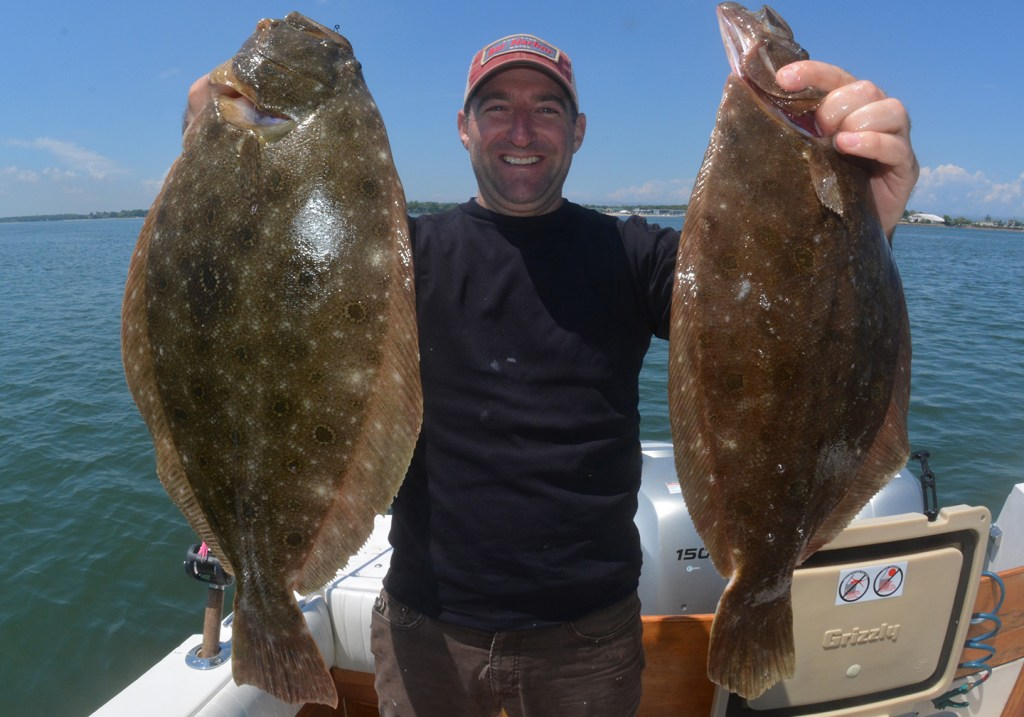 A happy angler in a cap standing at the back of a fishing charter boat and holding up two large Summer Flounder, also known as Fluke.
