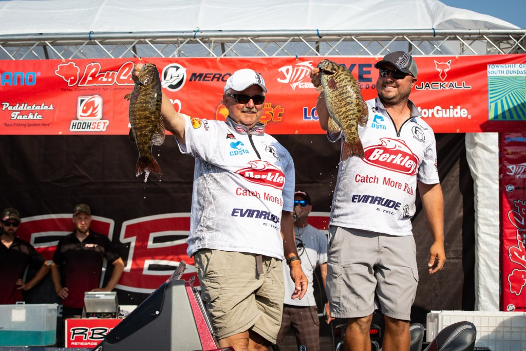 Two anglers holding trophy Smallmouth Bass on the stage at the Thousand Islands Open tournament