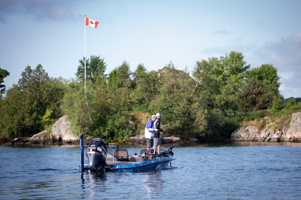 Two anglers on a bass fishing boat on Lake Ontario, with a Canadian flag flying behind them