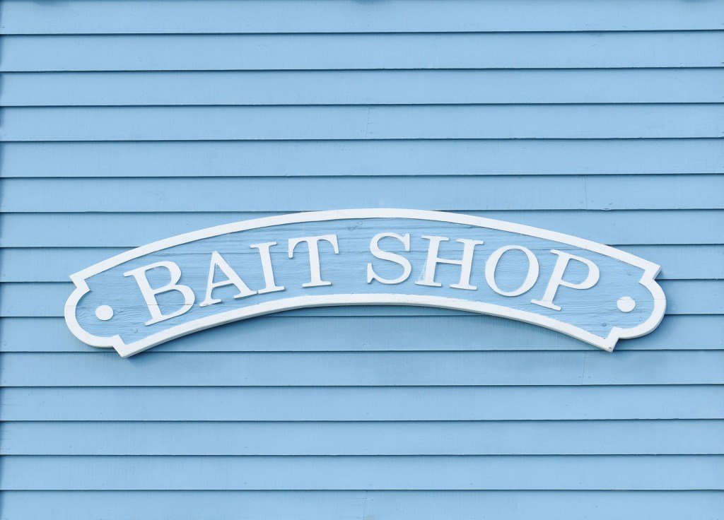 A sign on a wooden wall advertising a bait shop