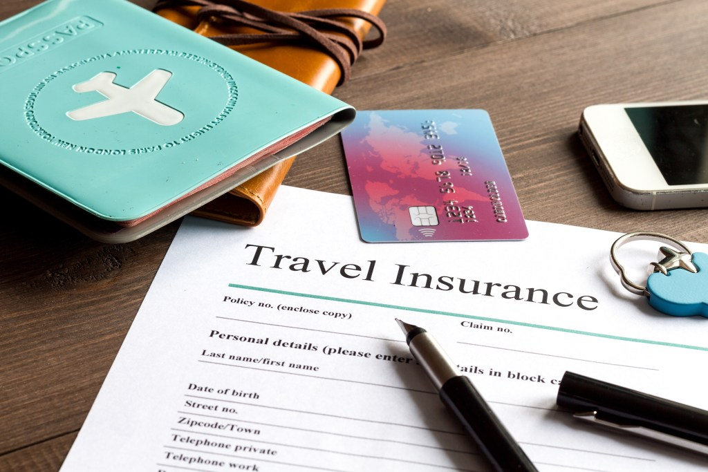A travel insurance form, with a pen, credit card, and mobile phone lying near it