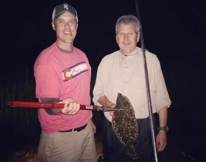Two men holding a gigging spear with a Flounder attached